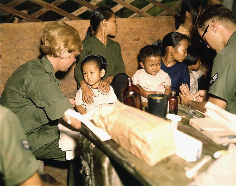 Second Lieutenant treats a Vietnamese child